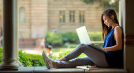 College student sitting outside on a bench with her laptop and a book and glasses by her side