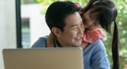 Young girl hugs her father while he works on his laptop
