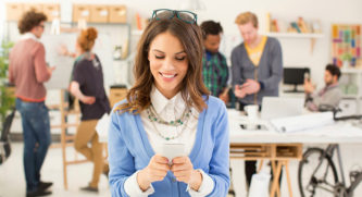 Woman smiling looking down at her phone, people are chatting in the background