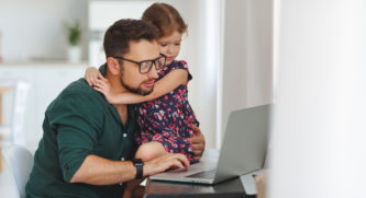 Dad looking at his computer while putting his arm around his daughter while she watches