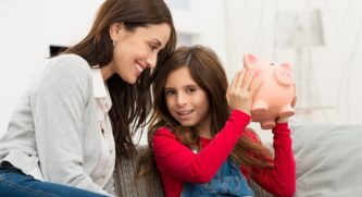 Mom watching her daughter shake her piggy bank