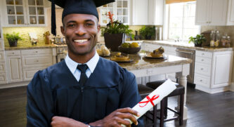 Man in graduation gown holding his diploma standing in the kitchen