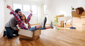 Woman sitting in a moving box with her boyfriend pushing her around their new house