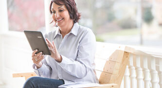Older Woman On Tablet On Bench