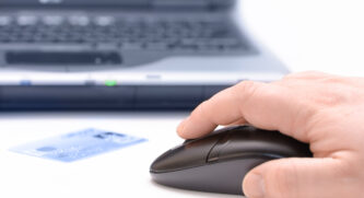 Person using a mouse with a credit card sitting in front and a laptop in the background