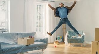 Man jumping up into the air in excitement in his new home surrounded by furniture covered in plastic